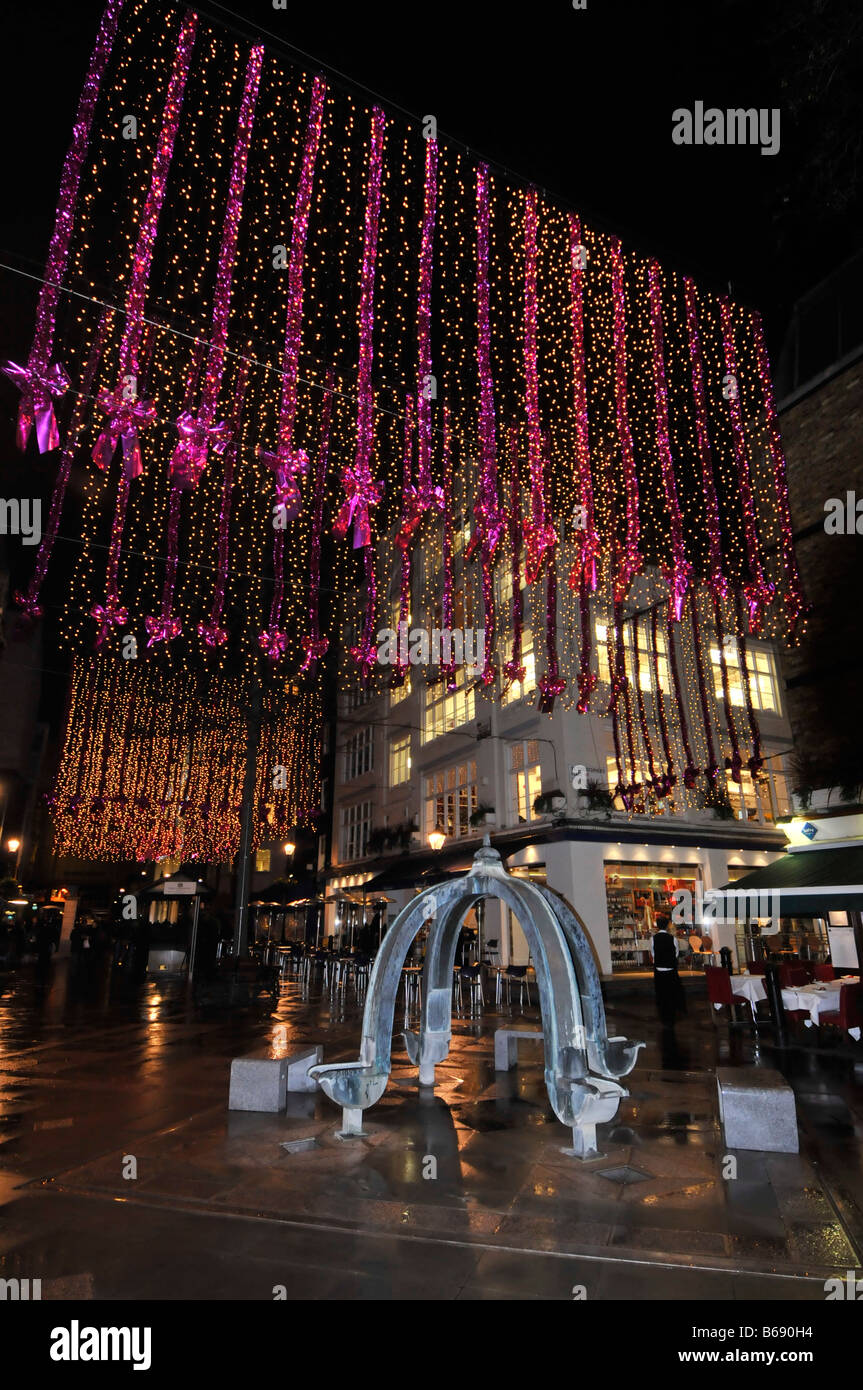 Christmas decorations in St Christophers Place a shopping and eating out area off 'Oxford Street' in a wet - Stock Image