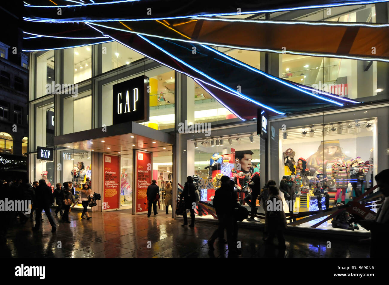 Shoppers outside the Gap fashions store Oxford Street London nighttime at Christmas in the rain - Stock Image