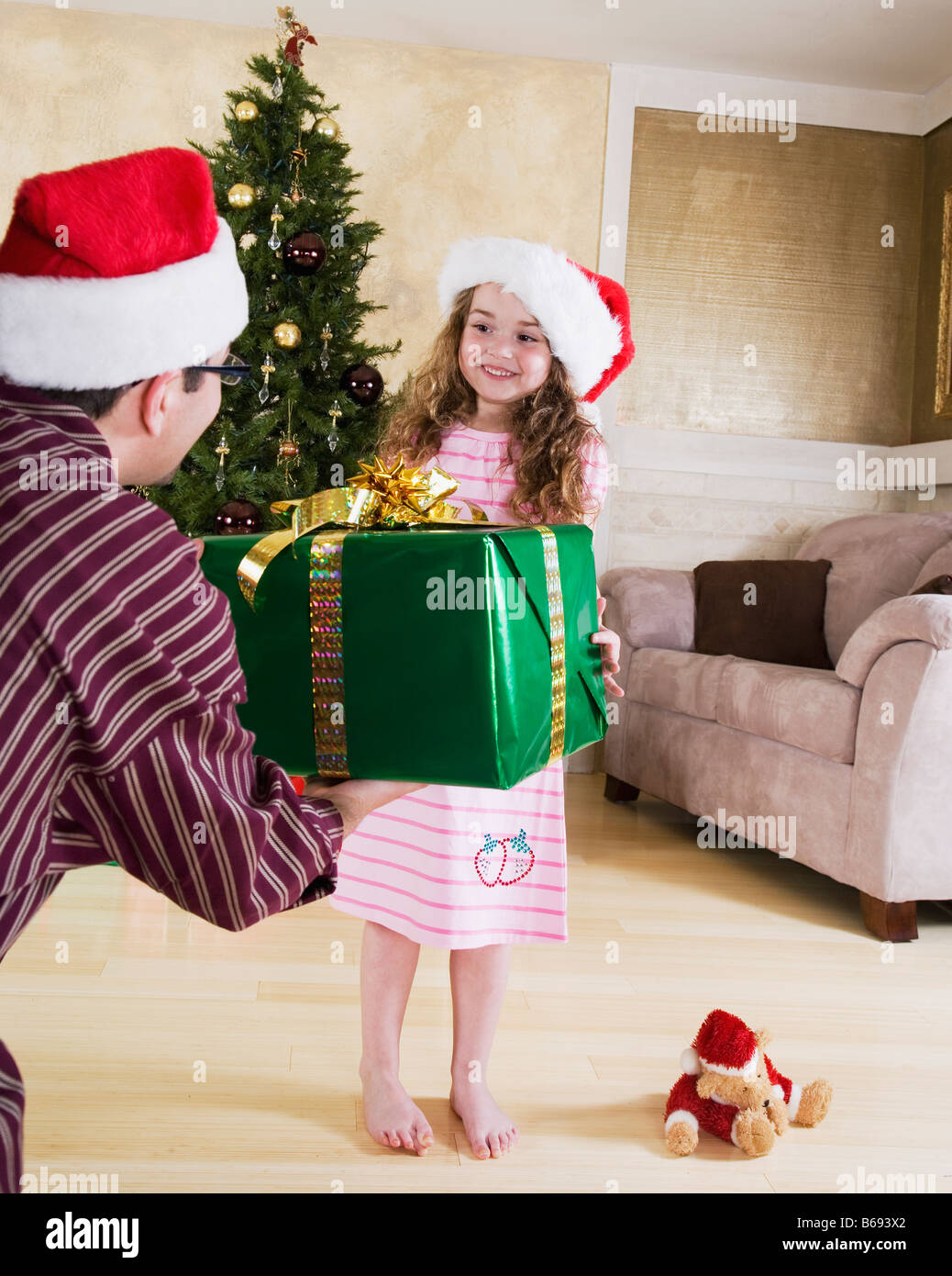 Father in Santa hat giving Christmas present to daughter (5-6) - Stock Image