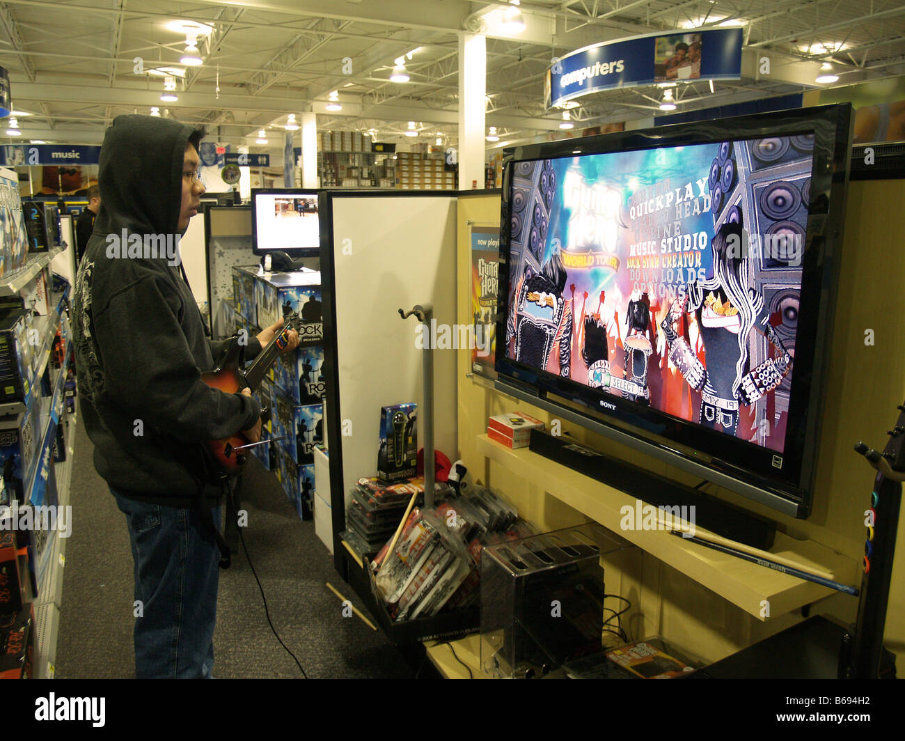 A teen male trying out the latest Guitar Hero at an electronics store display. - Stock Image