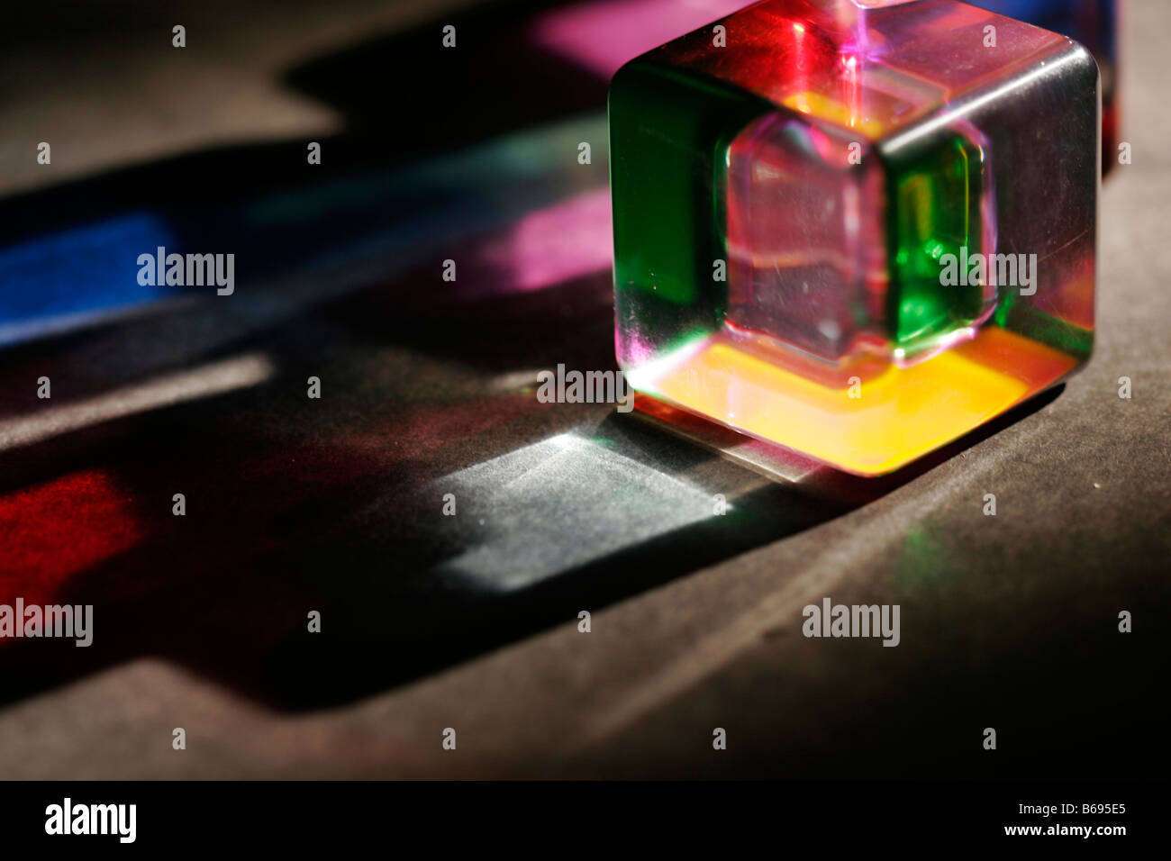 Colored acrylic cube with light shining through with colors spilling onto the table - Stock Image
