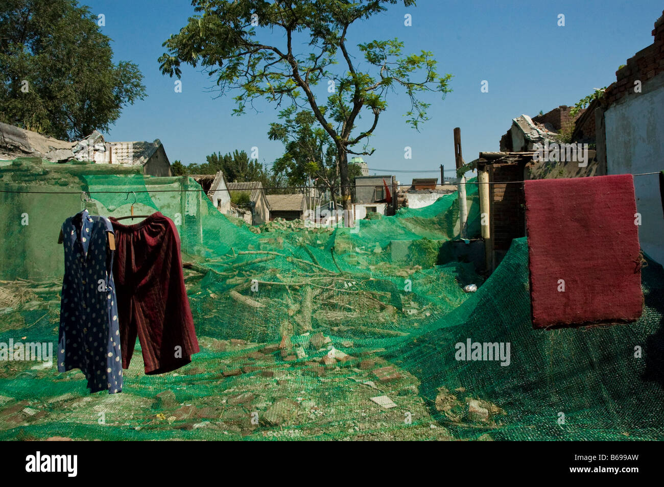 green plastic net covering demolished hutong rubble - Stock Image