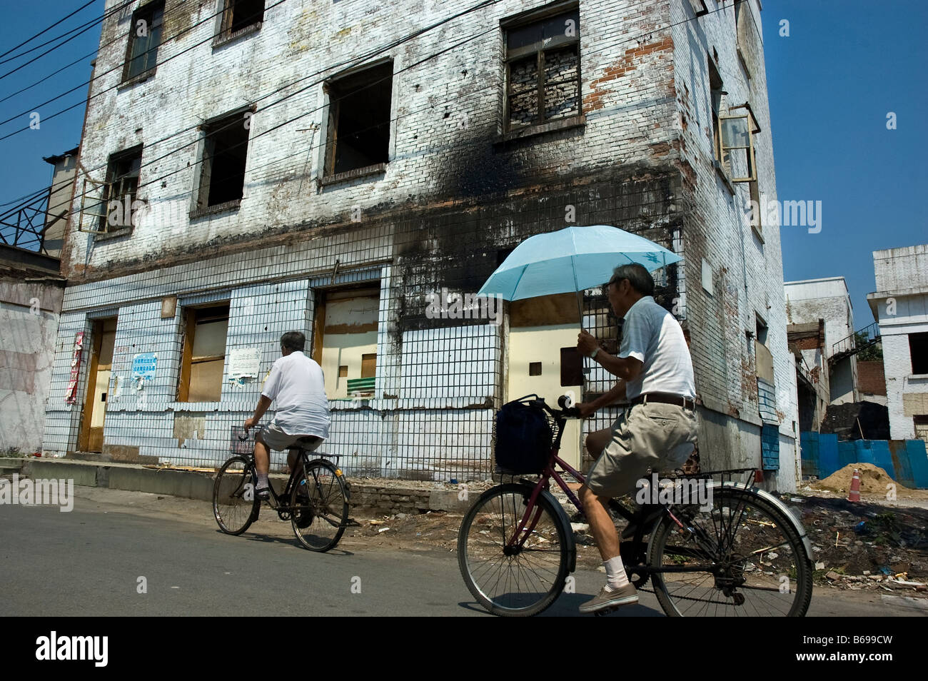 two bicycles pass by a building prepared to be demolished in hutong area in beijing - Stock Image