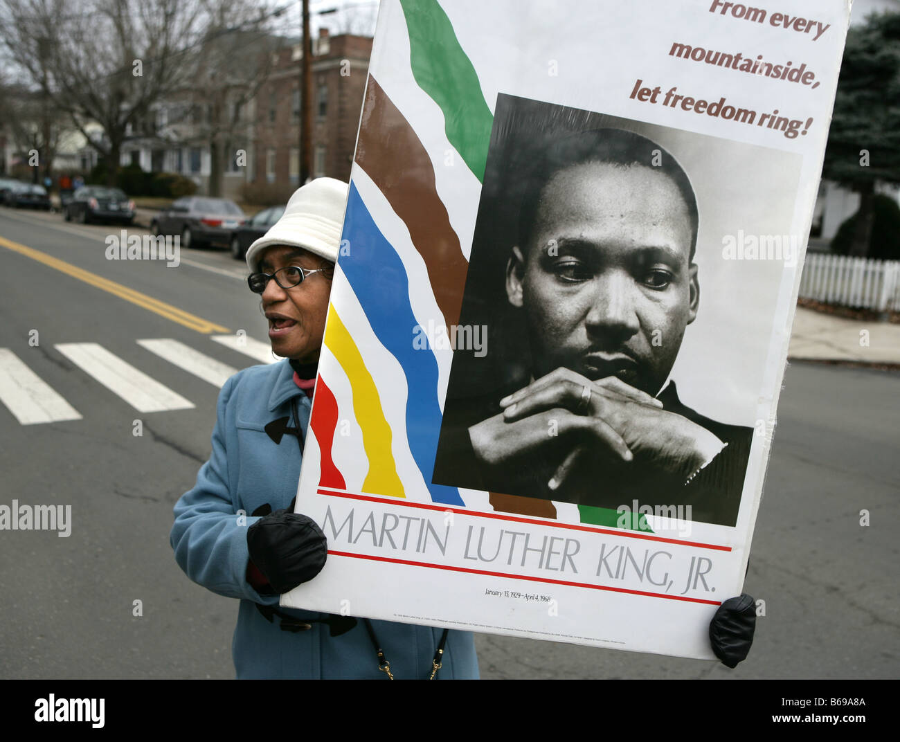A woman holds a Dr. Martin Luther King poster during a parade during Martin Luther King Holiday in the USA. New - Stock Image