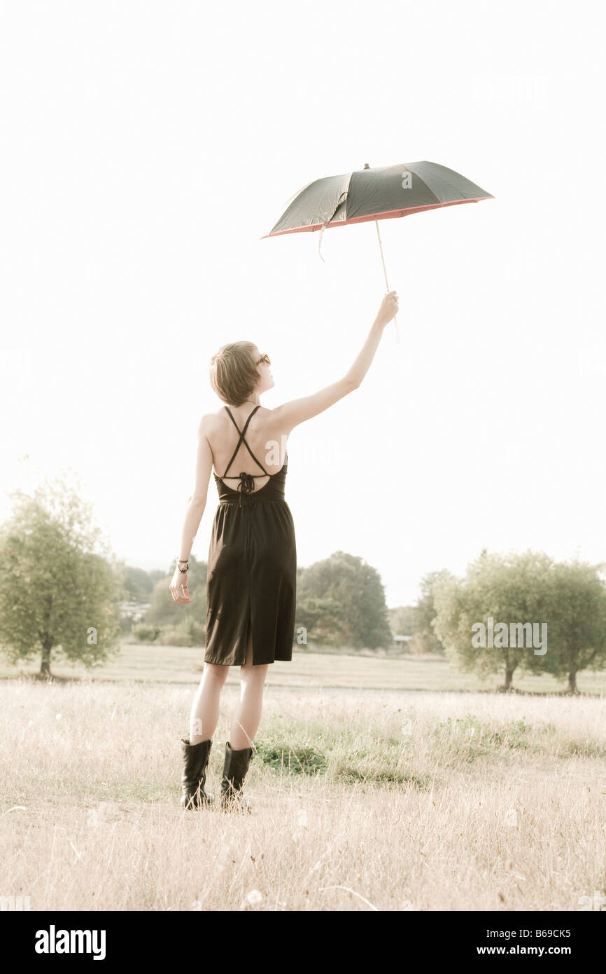 Woman holding an umbrella in a field - Stock Image