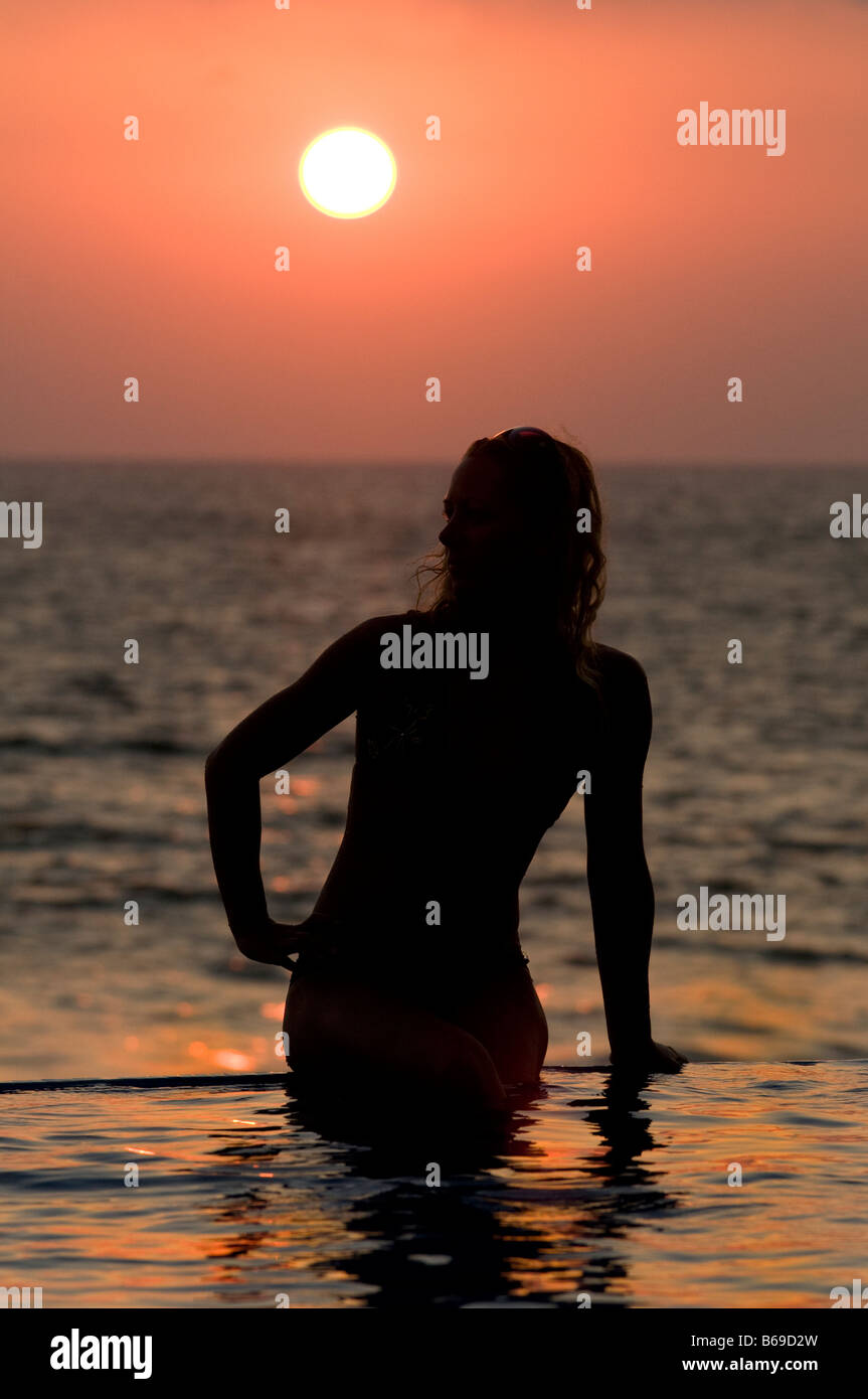silhouette of woman on infinity swimming pool, Puerto Vallarta, Mexico at sunset - Stock Image