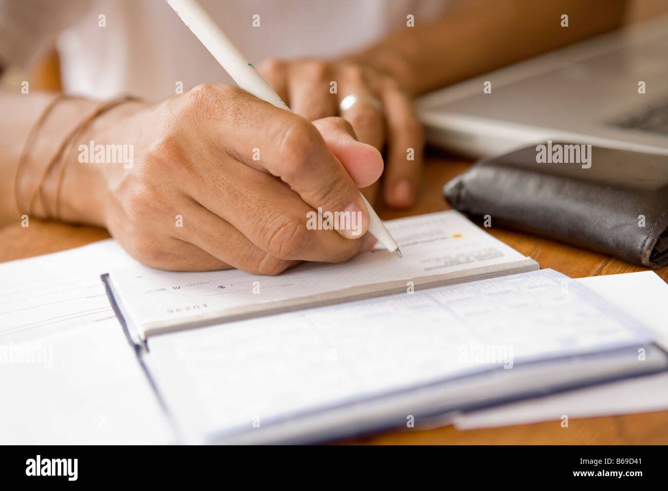 Man signing a check and preparing home finance budget Stock Photo