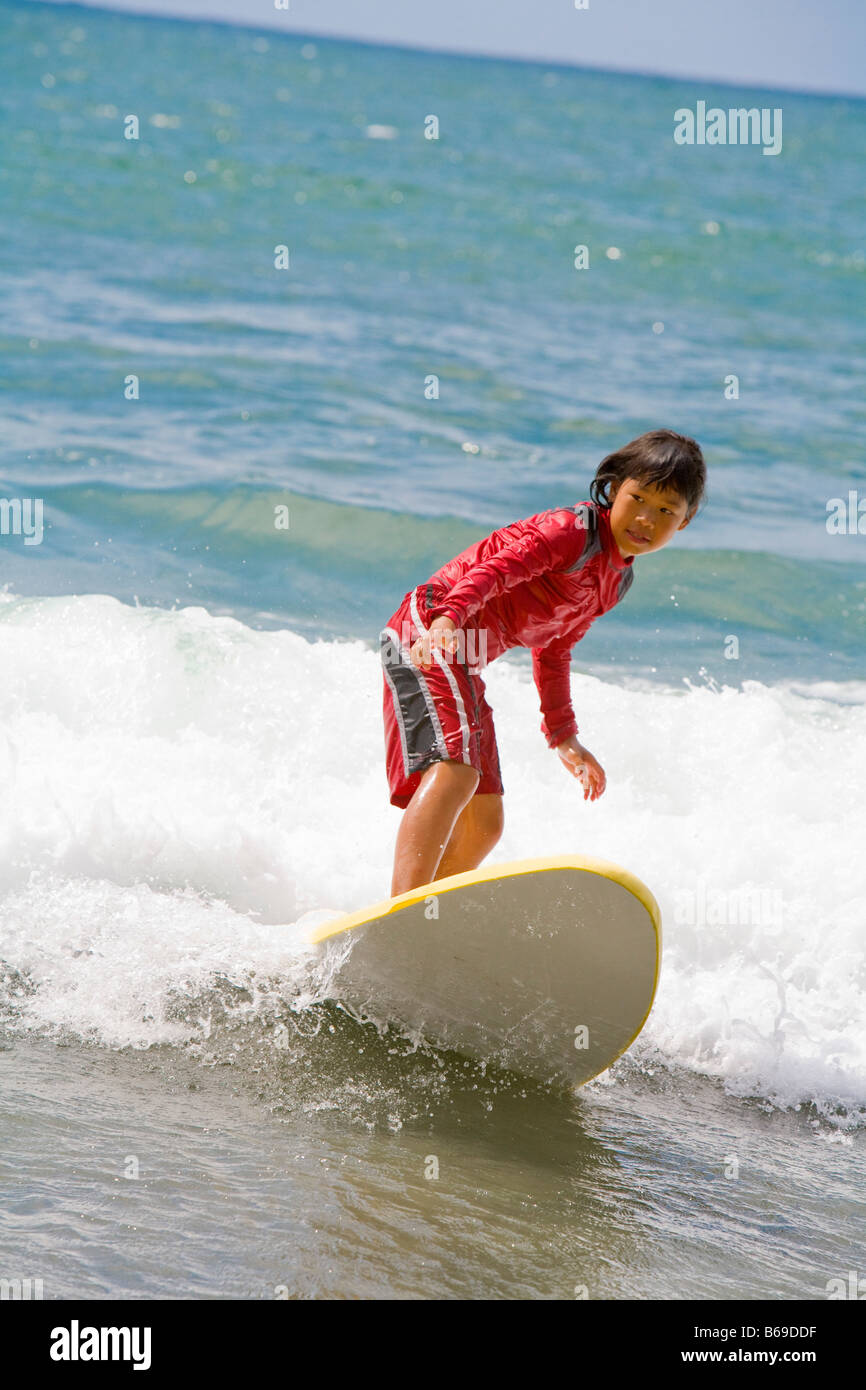 Girl surfing in the sea - Stock Image