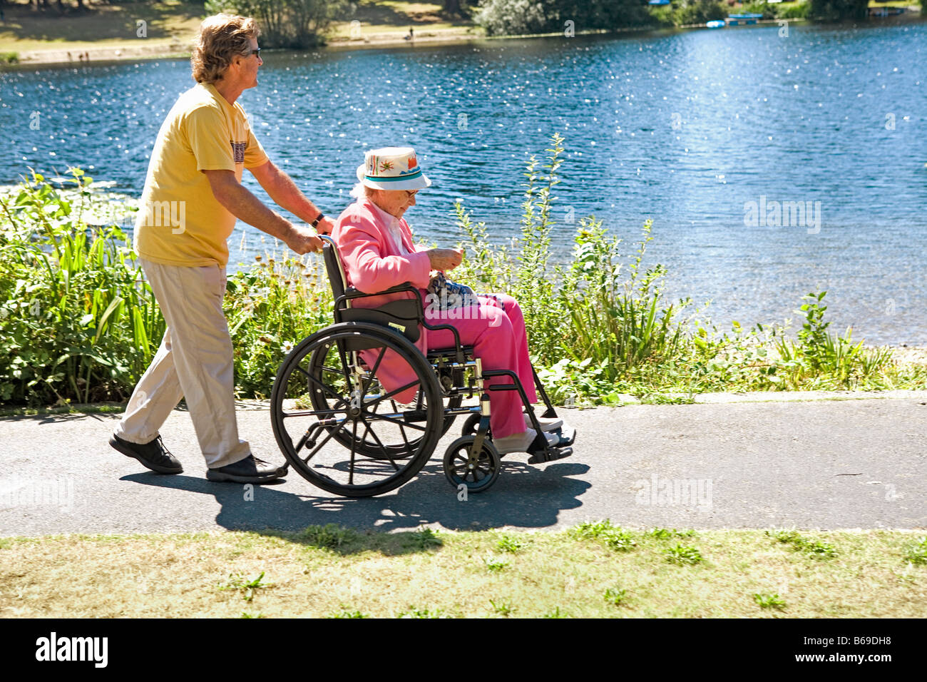 Man pushing his mother sitting in a wheelchair - Stock Image