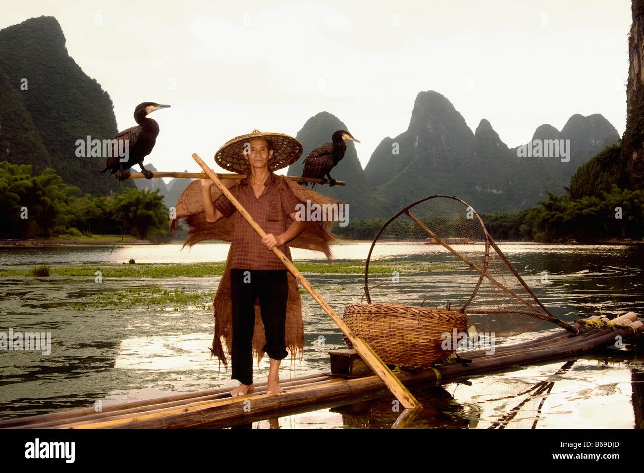 Senior man on a bamboo raft with a hill range in the background, Guilin Hills, XingPing, Yangshuo, Guangxi Province, Stock Photo