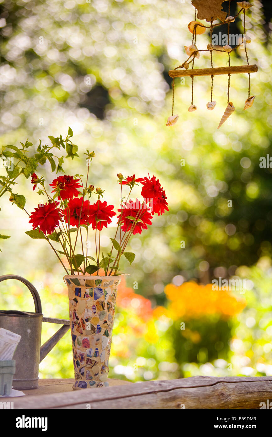 Watering can with a vase of flowers and a wind chime Stock Photo