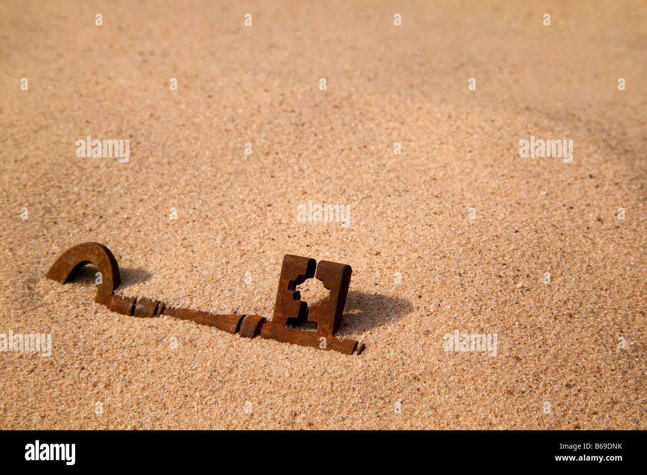 A rusty old key buried in the sand - Stock Image