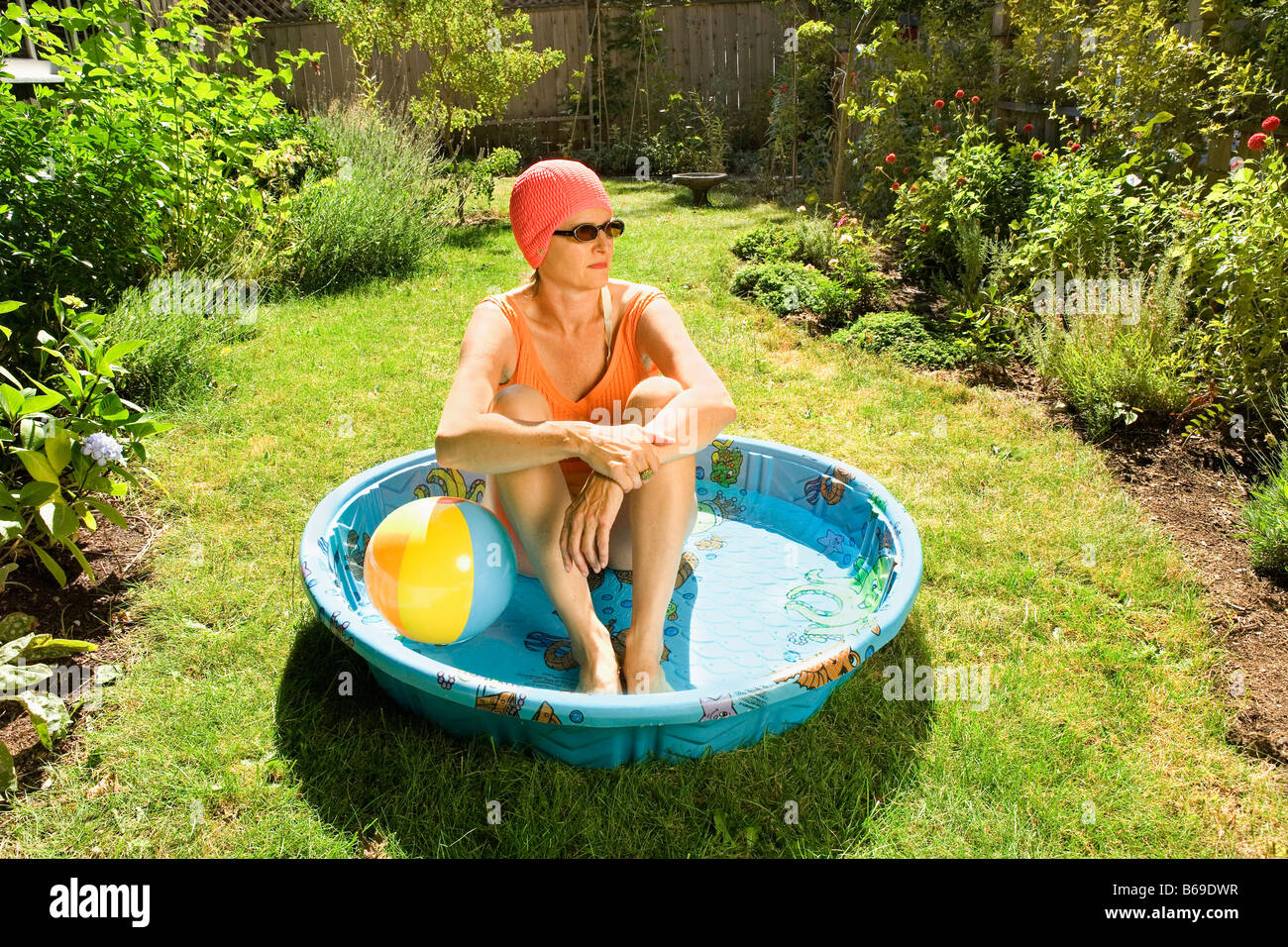 Woman sitting in a wading pool - Stock Image