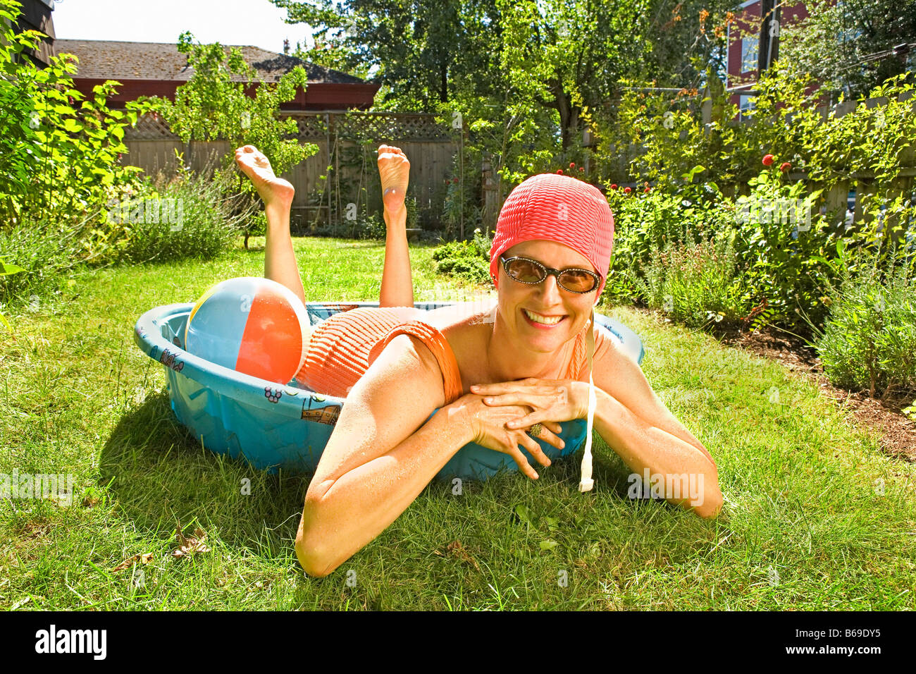 Woman lying in a wading pool and smiling - Stock Image