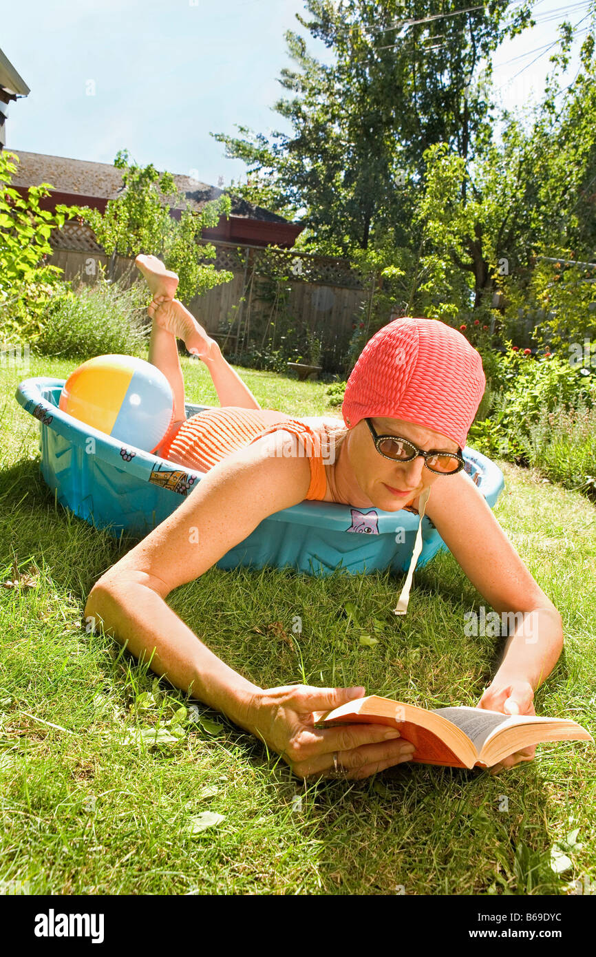 Woman lying in a wading pool and reading a book - Stock Image