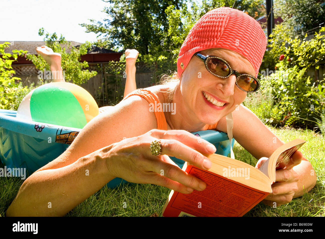 Woman reading a book in a wading pool - Stock Image