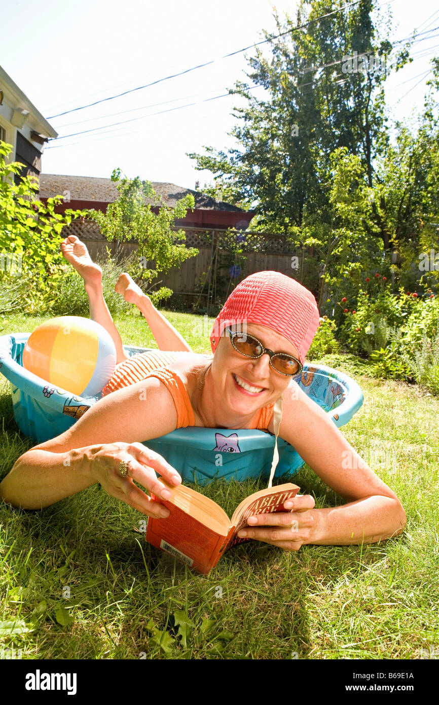 Woman holding a book in a wading pool - Stock Image