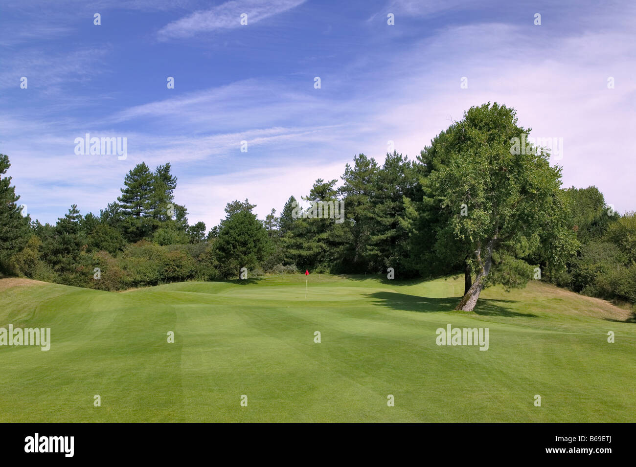 View from the fairway approaching the green with a red flag on a well maintained golf course - Stock Image