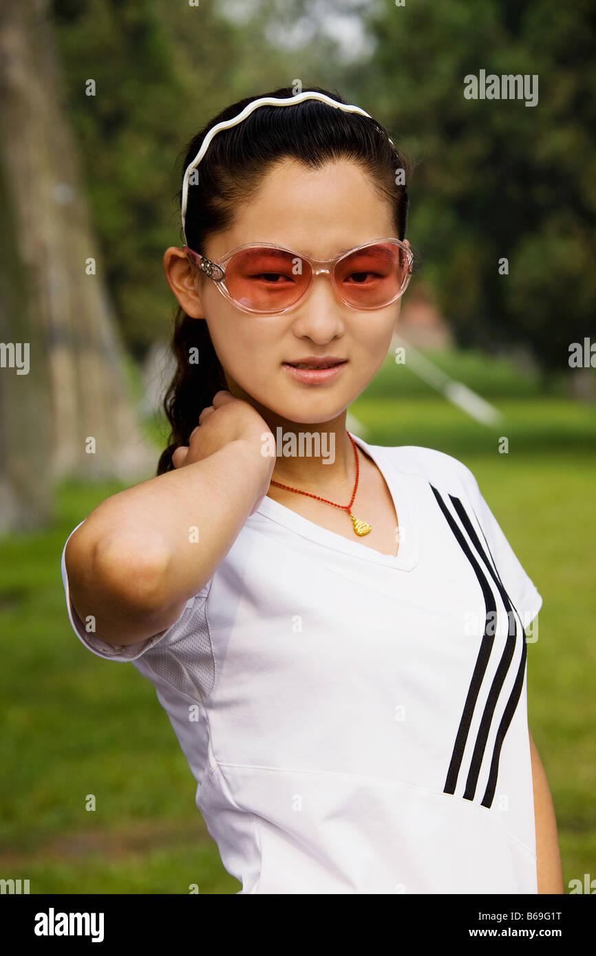 Close-up of a young woman wearing sunglasses, Qufu, Shandong Province, China - Stock Image