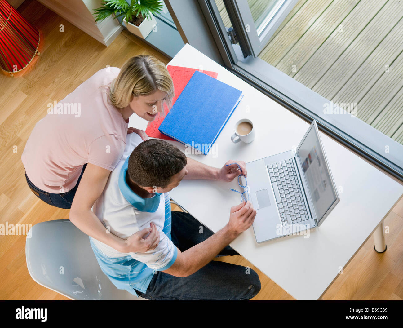 A couple looking at a laptop - Stock Image
