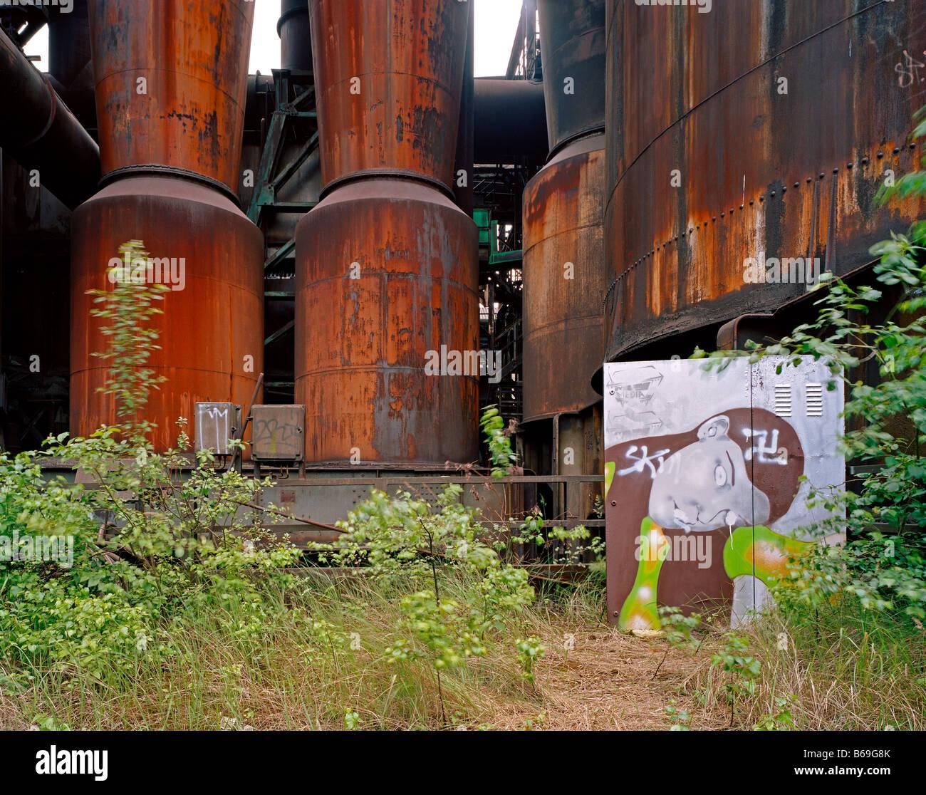 locker at Phoenix stellworks with graffitys and sprayed swastikas Metallspind vor rostigem Hochofen mit Graffiti - Stock Image