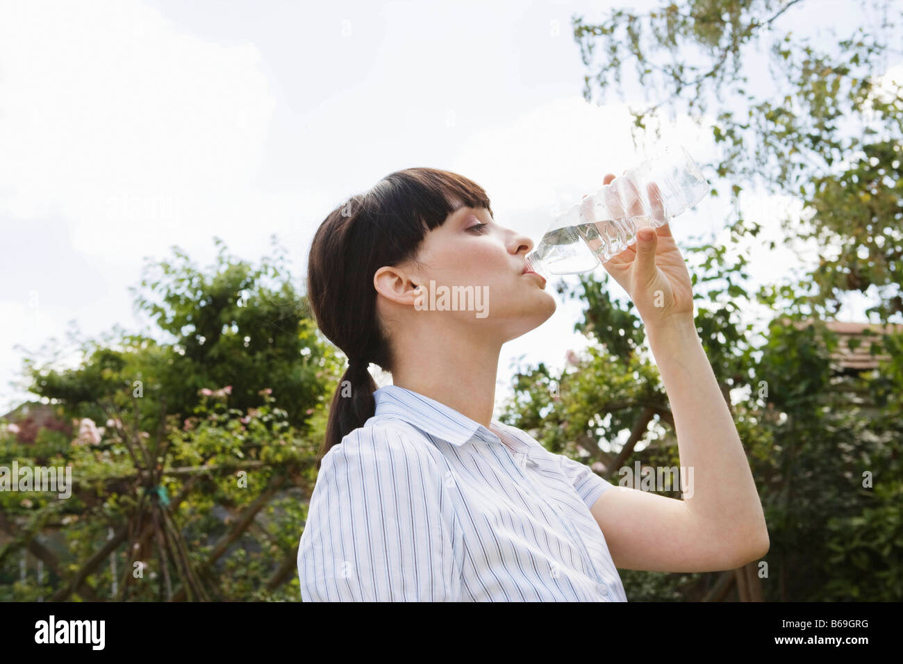 Woman drinking from water bottle in park - Stock Image