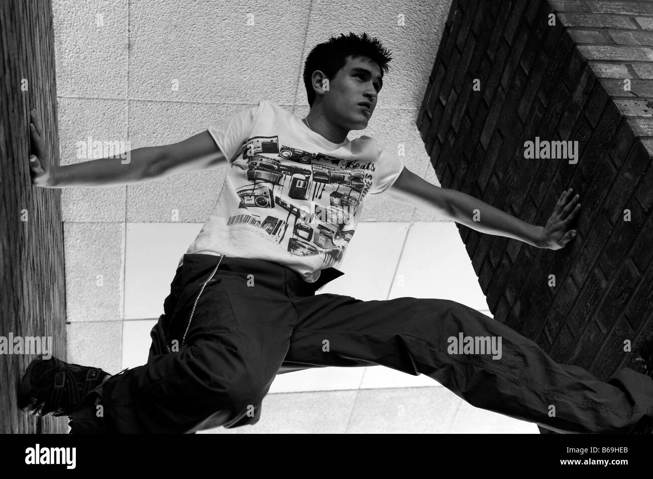 Holding the walls apart - a demonstration of parkour techniques - Stock Image