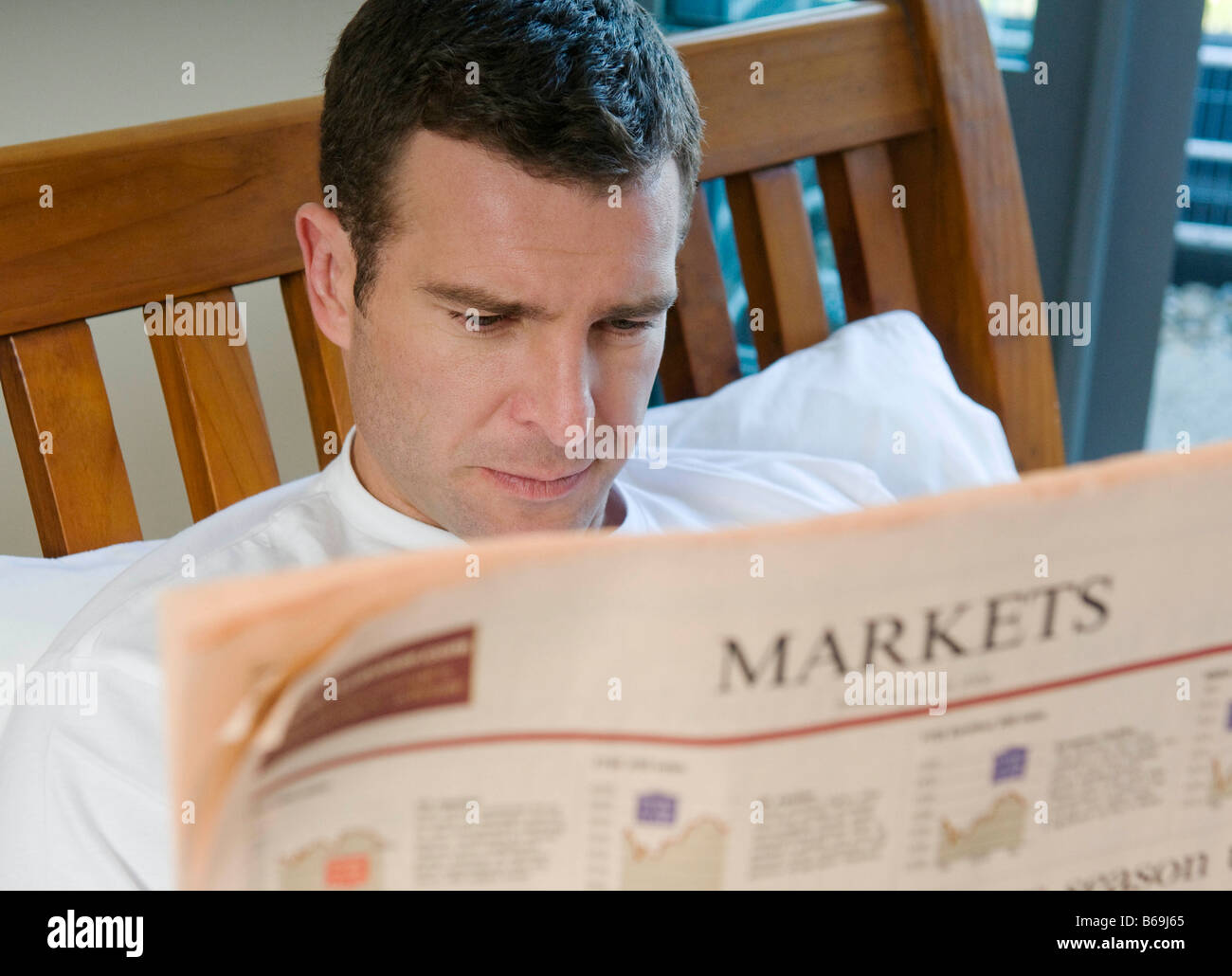 Man reads financial paper in bed Stock Photo