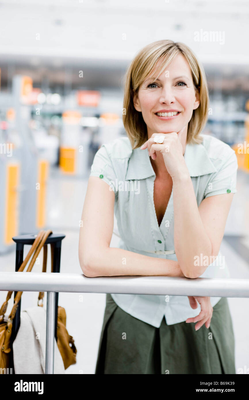 Woman smiling leaning onto a rail - Stock Image