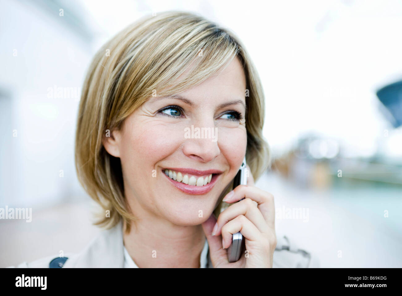 Woman smiling talking on cell phone - Stock Image