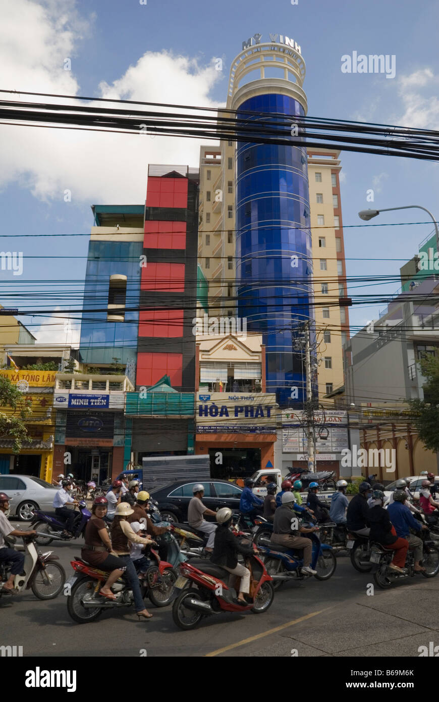 Electricity lines above a chaotic traffic clogged street in front of a modern building in Ho Chi Minh City, Vietnam - Stock Image