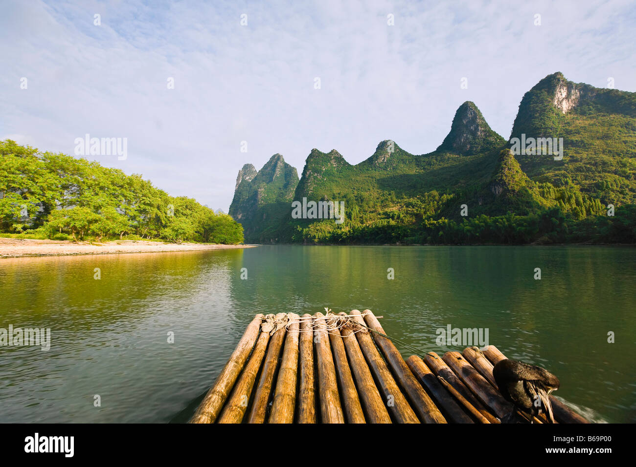 Bamboo raft in a river with a hill range in the background, Guilin Hills, XingPing, Yangshuo, Guangxi Province, - Stock Image