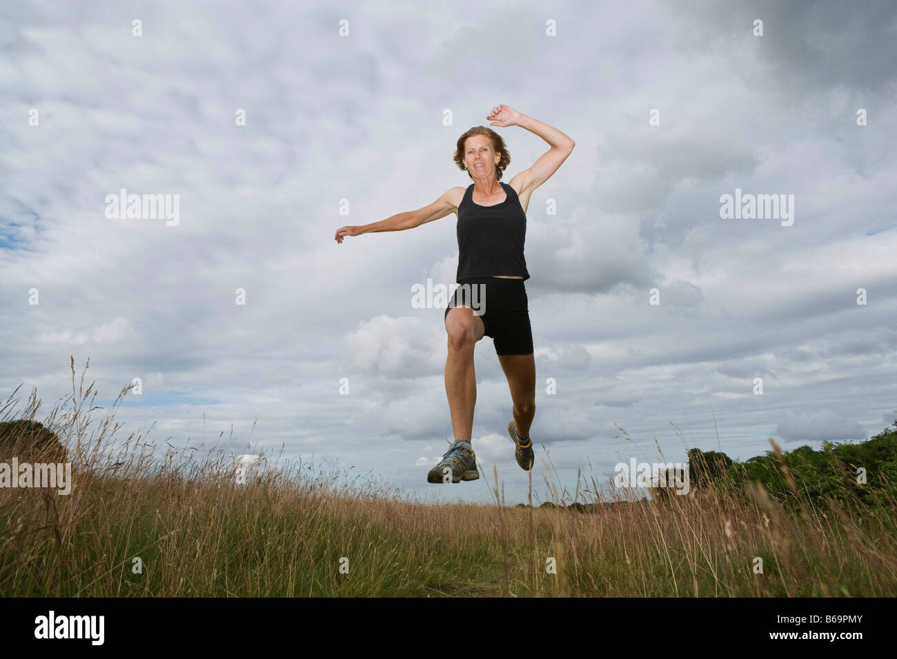 Woman running on dirt track - Stock Image