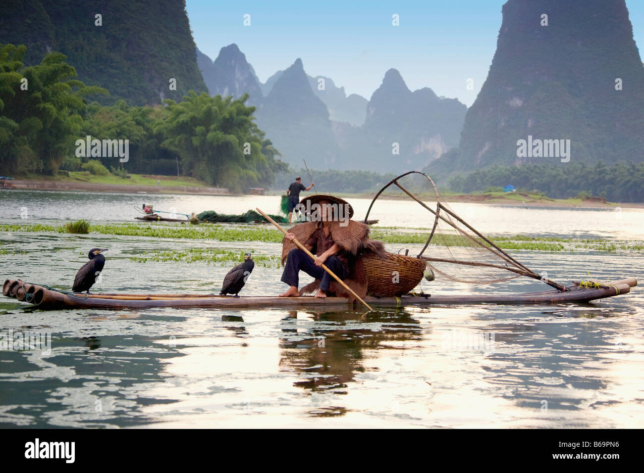 Fisherman fishing in a river with a hill range in the background, Guilin Hills, XingPing, Yangshuo, Guangxi Province, - Stock Image