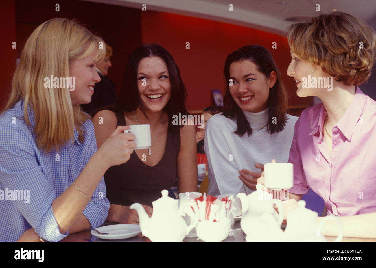 four young women chatting over a cup of tea - Stock Image