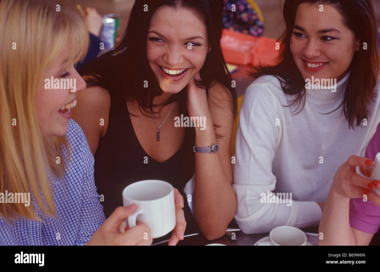 three women chatting over a coffee - Stock Image