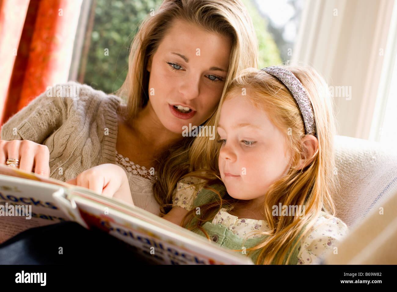 mother reading a book with her daughter Stock Photo