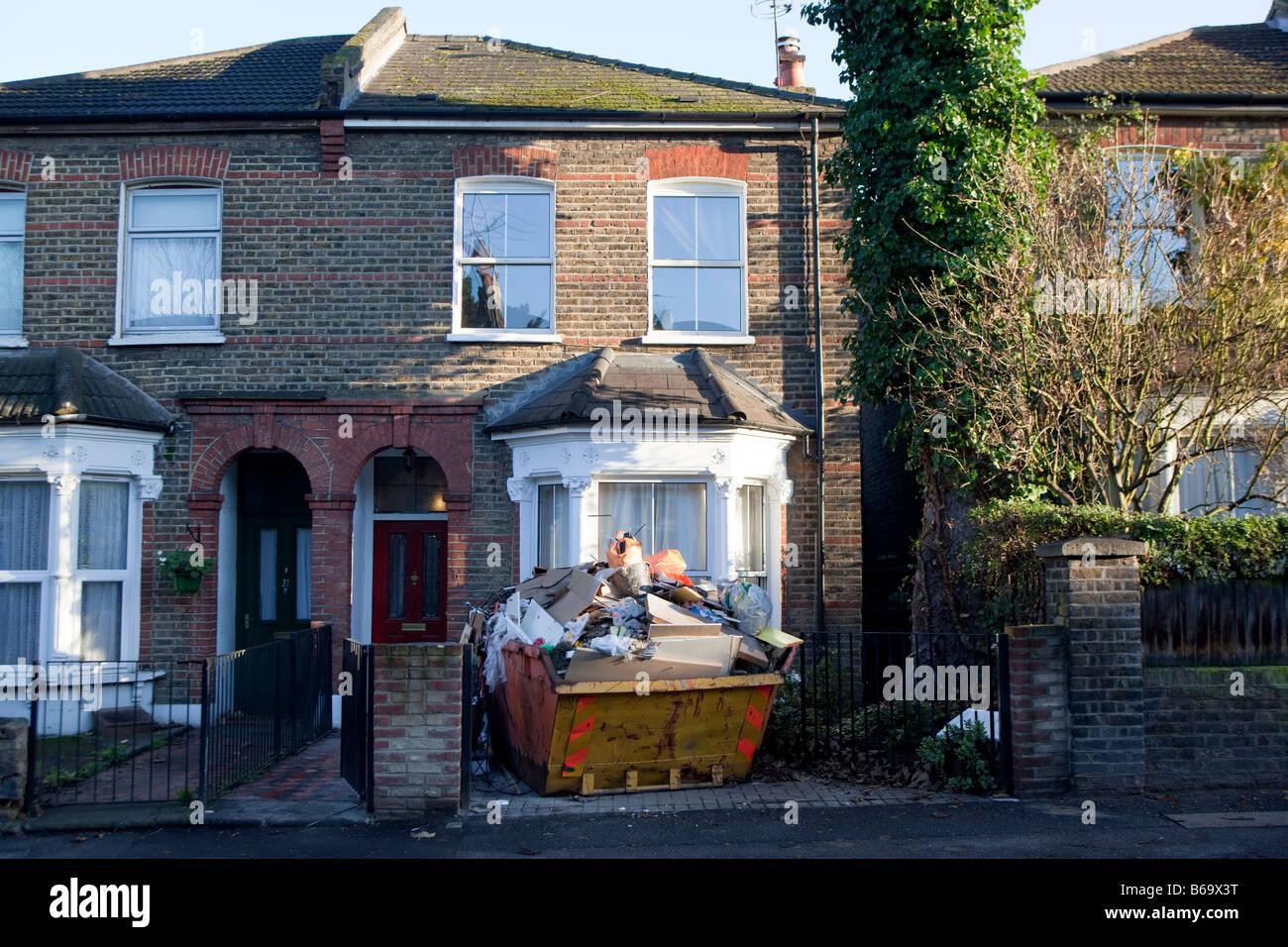 skip outside edwardian victorian semi detached terrace house - Stock Image