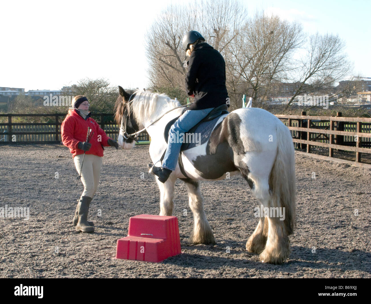 AN INSTRUCTOR TEACHING SCHOOL CHILDREN TO RIDE AT A RIDING SCHOOL LONDON, UK. Photo ©Julio Etchart - Stock Image