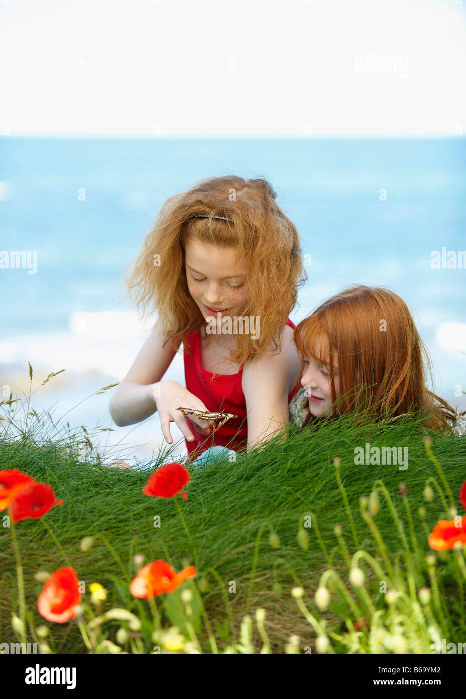 2 girls watching butterfly - Stock Image