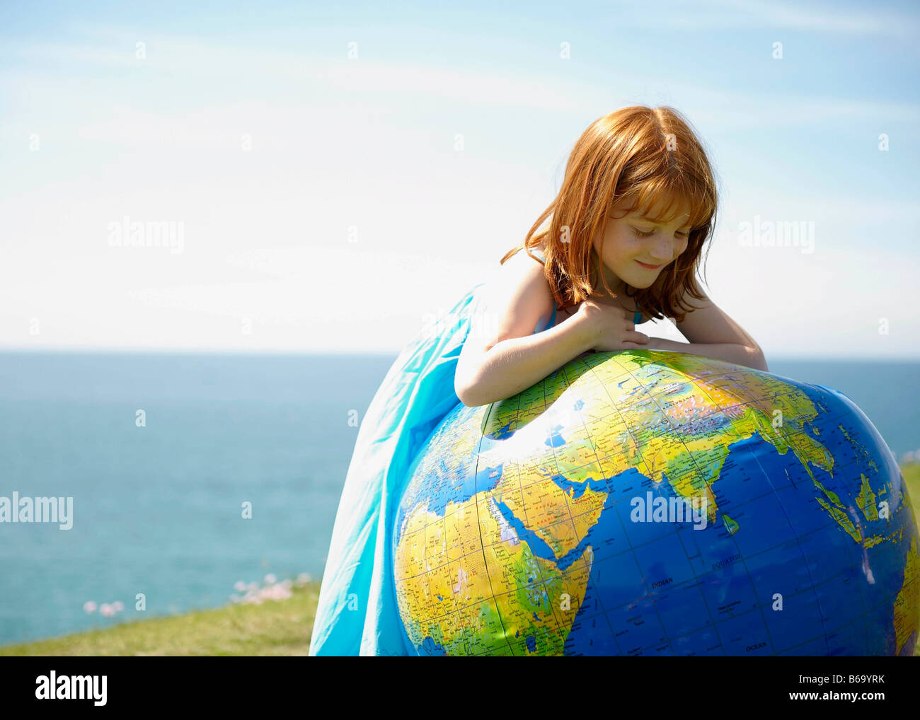 Young girl looking at inflatable globe - Stock Image