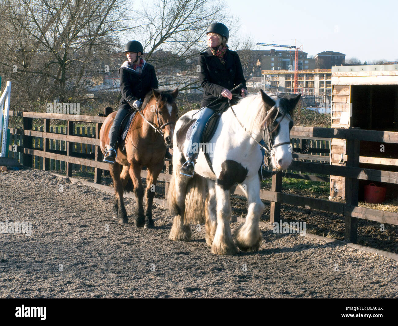 INSTRUCTOR TEACHING SCHOOL CHILDREN TO RIDE AT A RIDING SCHOOL LONDON, UK. Photo ©Julio Etchart - Stock Image