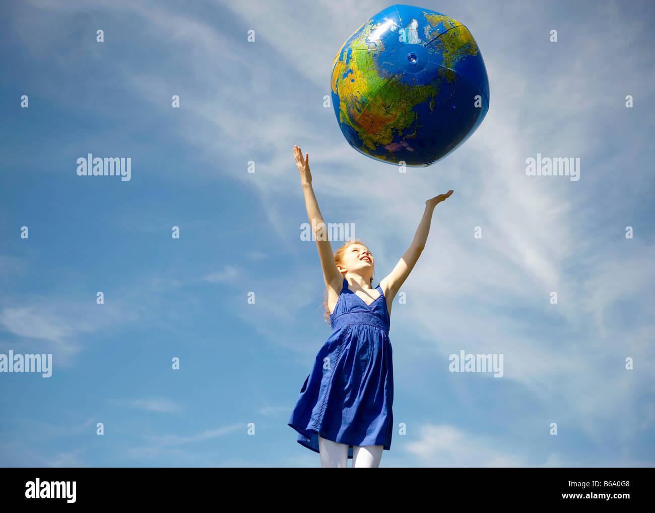Young girl throwing inflatable globe - Stock Image