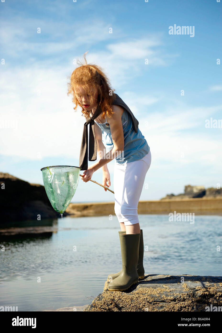 Young girl looking in net at rock pool - Stock Image