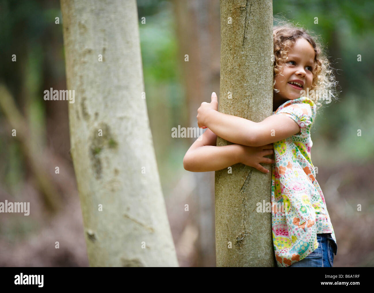 Young girl hugging tree smiling - Stock Image