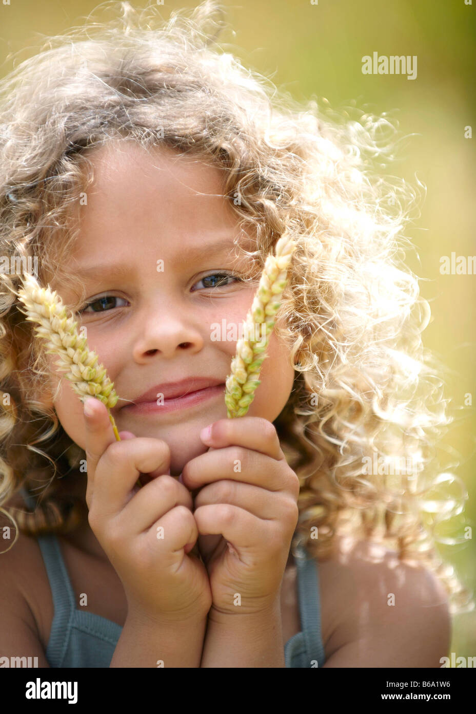 Young girl holds up ears of corn - Stock Image