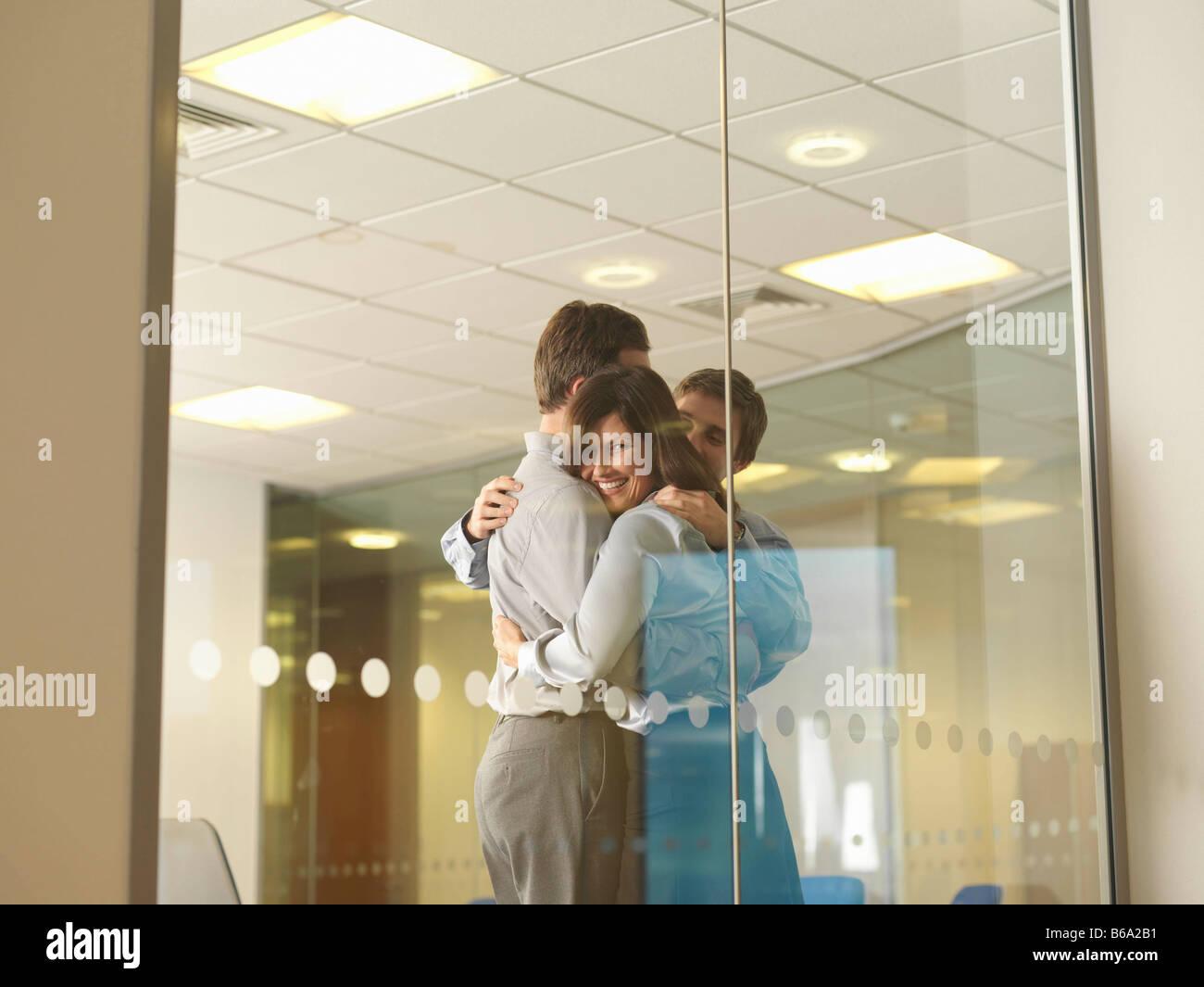 Office staff group hug - Stock Image