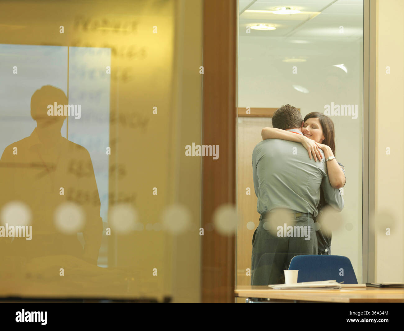 Office couple cuddling - Stock Image
