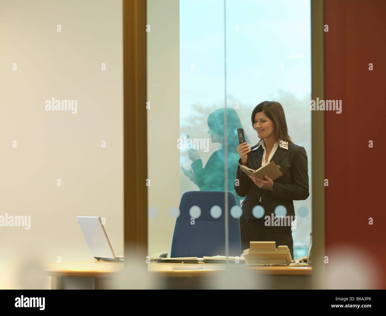 Business woman dialing mobile - Stock Image
