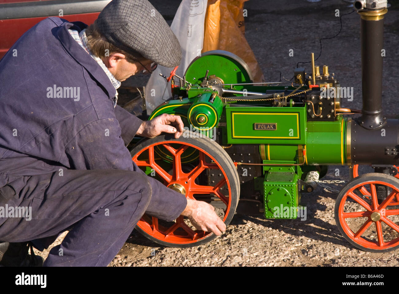 enthusiast cleaning his small steam engine - Stock Image